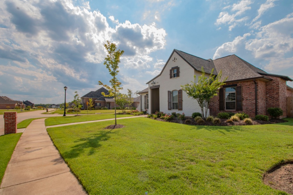 Home in subdivision with nice lawn and blue skies